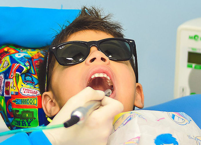 Cool kid wearing sunglasses having his dental check up with dental creations of daytona beach, fl
